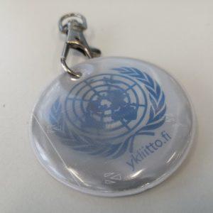 Valkoinen, pyöreä pehmoheijastin, jossa YK:n sininen maapallologo. Yläosassa metalliklipsikiinnitys