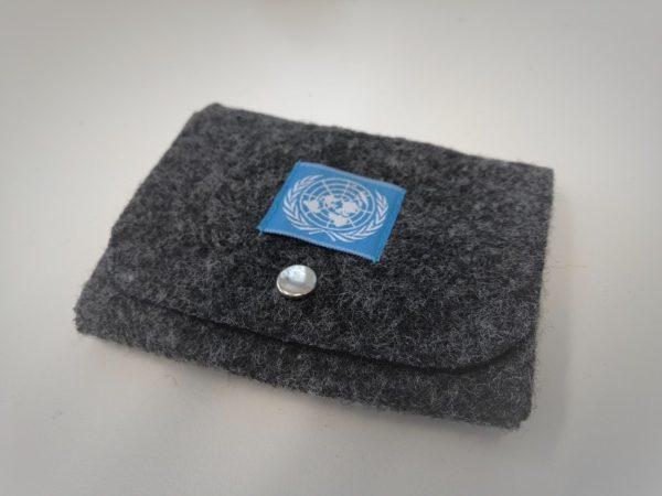 Tummanharmaa huovasta tehty rahakukkaro, jonka kannessa metallinen avattava neppari. Kanteen ommeltu kankainen neliö, jossa sinisellä pohjalla YK:n logo