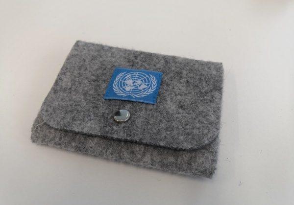Vaaleanharmaa huovasta tehty rahakukkaro, jonka kannessa metallinen avattava neppari. Kanteen ommeltu kankainen neliö, jossa sinisellä pohjalla YK:n logo