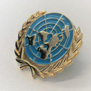 Kullattu rintapinssi, jossa sininen, litteä YK:n maapallotunnus