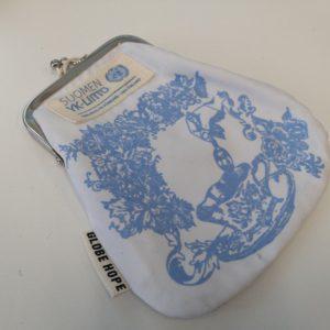 Valkoinen kankainen rahakukkaro, jossa vaalean sinistä koristeornamenttia ja kangaspalalla YK-liiton logo